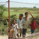 Curious Cambodian children eye peak through the fences of The Killing Fields