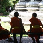 Novice monks sit outside a Buddhist temple